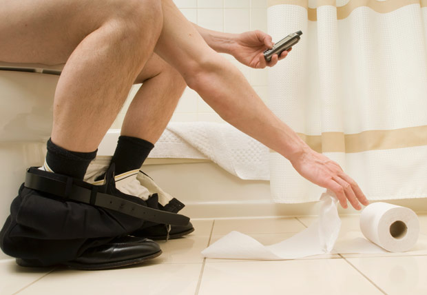 man in toilet with mobile